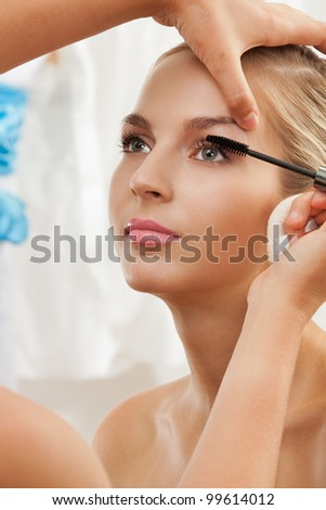 Portrait of a model having separating and curling lashes with mascara brush by makeup artist