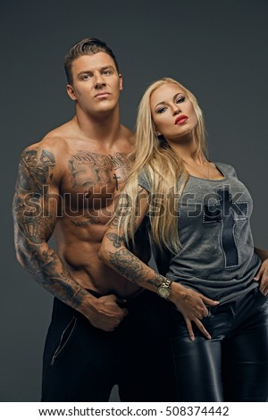 Portrait of a modern couple of shirtless brutal tattooed male and sensual blonde female isolated on grey background.
