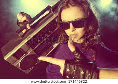 Portrait of a modern girl with tape recorder over grunge background. Street urban style. - stock photo