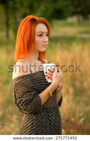 Portrait of a modern stylish woman who drinks coffee or tea from a white paper disposable cup. Concept - tea or coffee. White cup in his hands. Young girl on the background of nature city park. - stock photo