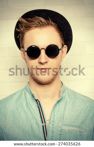 Portrait of a modern young man standing by the brick wall. Beauty, fashion. Hipster style. - stock photo