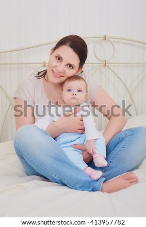 Portrait of a mother and baby in the bedroom. - stock photo