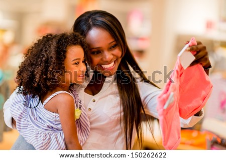 Portrait of a mother and daughter shopping for clothes  - stock photo