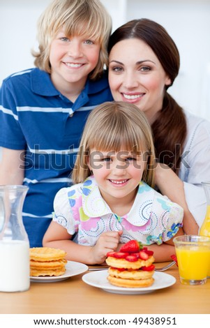 Portrait of a mother and her children having breakfast in the kitchen - stock photo