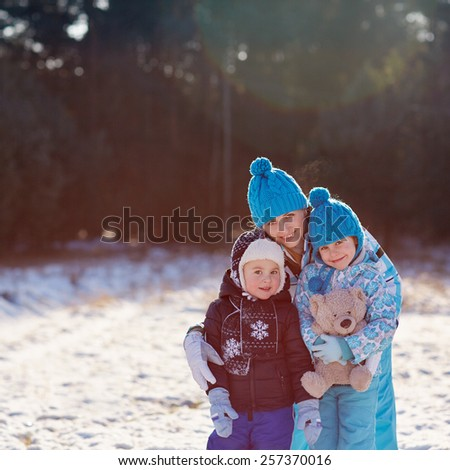 Portrait of a mother and her cute little son and daughter hugging a teddy bear outdoors on a winter's day
