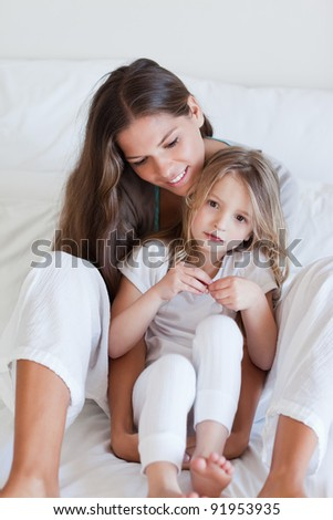 Portrait of a mother and her daughter posing on a bed looking away from the camera