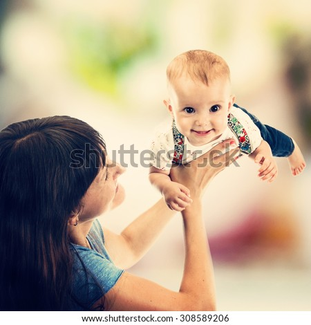 Portrait of a mother playing with little baby girl, on blurred background, instagram style toned - stock photo