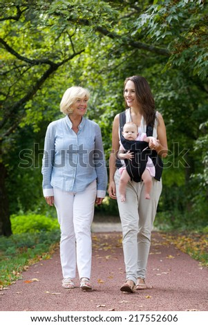 Portrait of a mother walking outdoors with grandmother and baby in sling - stock photo