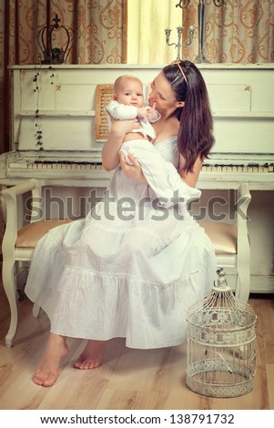 Portrait of a mother with a newborn baby on the background piano - stock photo
