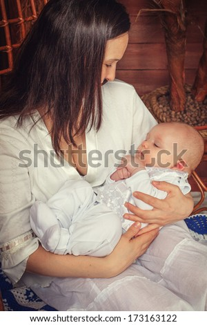 Portrait of a mother with a sleeping baby in her arms in the Hawaiian interior - stock photo