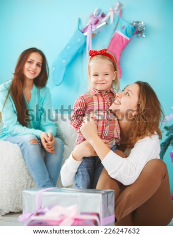 Portrait of a mother with baby daughter and teen daughter being close and hugging at home near the Christmas tree being happy and joyful - stock photo