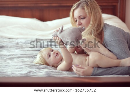 Portrait of a mother with her baby in bedroom at home - stock photo