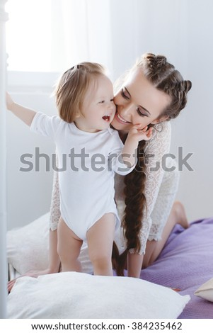Portrait of a mother with her 9 months old baby at home. Happy child near to mum in her room. Portrait of a mother with her newborn baby. Playing together. Happy family. Woman with child on bed  - stock photo