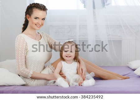Portrait of a mother with her 9 months old baby at home. Happy child near to mum in her room. Portrait of a mother with her newborn baby. Playing together. Happy family. Woman with child on bed