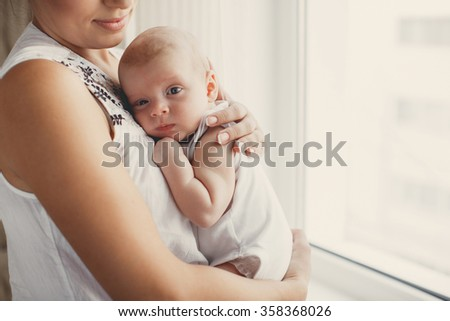Portrait of a mother with her 3 months old baby. Mother holding head of her newborn son in hands. The baby on hands at mum. Loving mother hand holding cute sleeping newborn baby.home portrait. love - stock photo