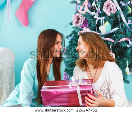 Portrait of a mother with teen daughter being close and hugging at home near the Christmas tree being happy and joyful - stock photo