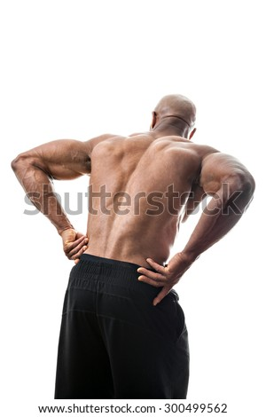Portrait of a muscle fitness man reaching for his lower back in pain - stock photo