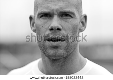 Portrait of a muscular athlete staring at camera intense - stock photo