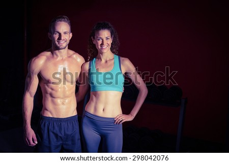 Portrait of a muscular couple on a shadow background