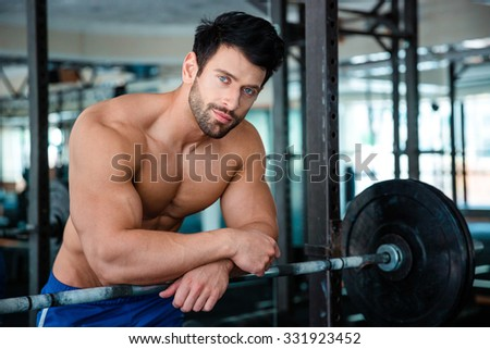 Portrait of a muscular male bodybuilder looking at camera in fitness gym - stock photo