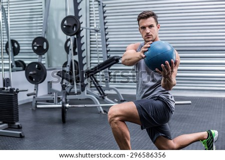 Portrait of a muscular man doing medecine ball exercises - stock photo