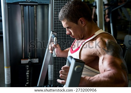 Portrait of a muscular man in the gym. A strong man bodybuilder on a simulator shakes muscles. fitness training