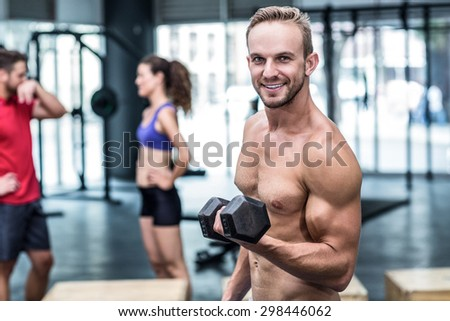 Portrait of a muscular man lifting a dumbbell - stock photo