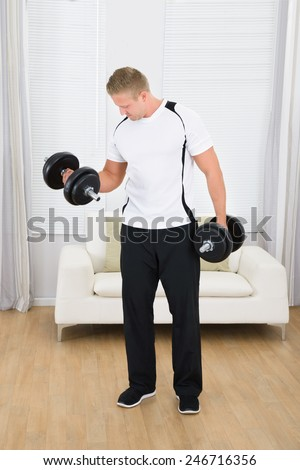 Portrait Of A Muscular Man Lifting Weights At Home - stock photo