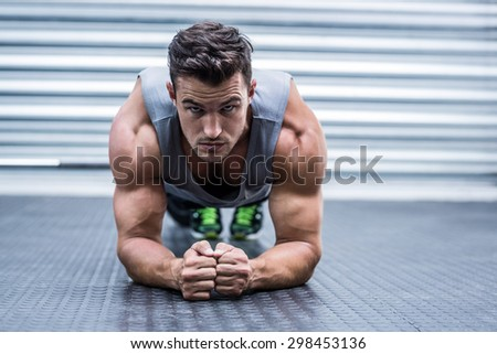 Portrait of a muscular man on plank position - stock photo