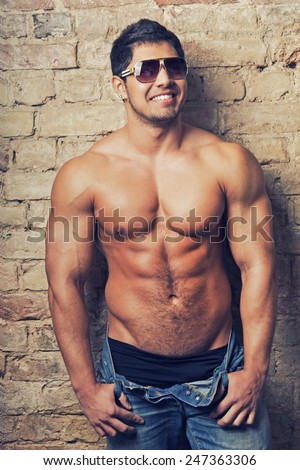 Portrait of a muscular man posing against old wall - stock photo