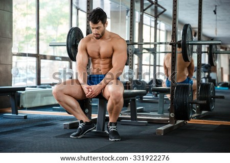 Portrait of a muscular man resting on the bench in fitness gym - stock photo