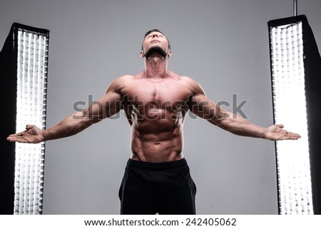 Portrait of a muscular man with his hands in the air at his sides on gray background - stock photo