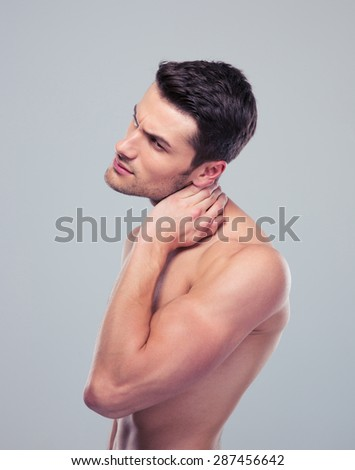 Portrait of a muscular man with neck pain over gray background