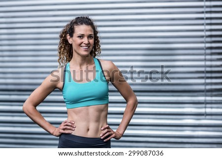 Portrait of a muscular woman with hands on hips - stock photo