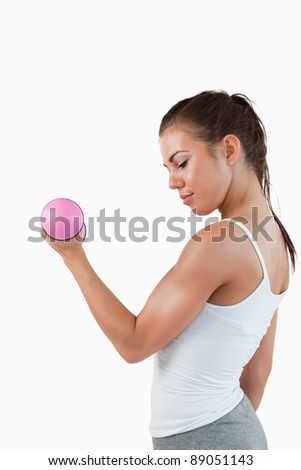 Portrait of a muscular woman working out with dumbbells against a white background