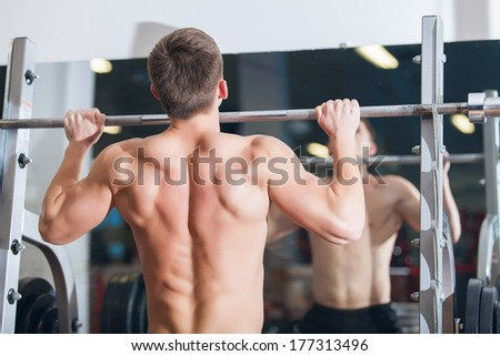 Portrait of a muscular young man in the gym - stock photo