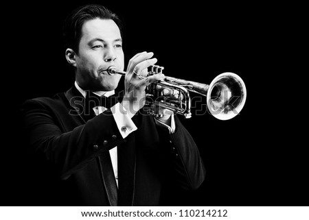 Portrait of a musician playing the trumpet. Black background. - stock photo