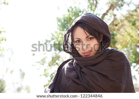 Portrait of a muslim young woman wearing a brown head scarf and smiling at the camera outdoors. - stock photo
