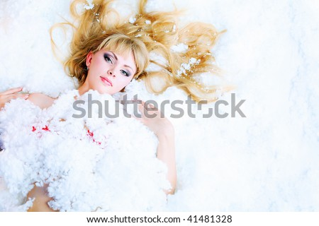 Portrait of a naked young woman lying under snow. - stock photo