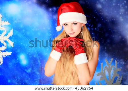 Portrait of a naked young woman wearing christmas cap and red gloves over sky of stars and snow. - stock photo