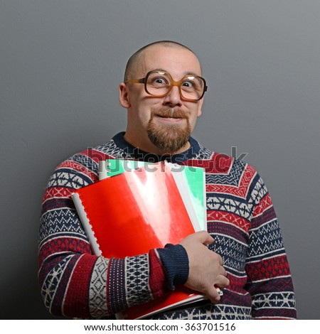 Portrait of a nerd holding book with retro glasses against gray background - stock photo