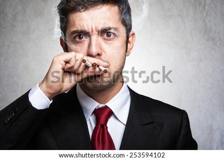 Portrait of a nervous man smoking many cigarettes - stock photo