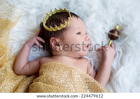 Portrait of a newborn baby boy with a golden crown - stock photo
