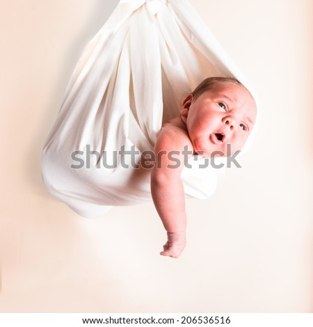 Portrait of a newborn baby in a white hammock or sling - stock photo