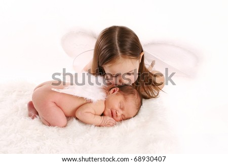 Portrait of a newborn baby with angel wings being kissed by big sister wearing white fairy wings - stock photo