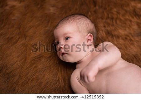 Portrait of a newborn caucasian girl lying on a dark background - stock photo