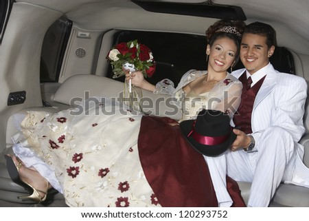 Portrait of a newlywed couple sitting  together in a car on their wedding day - stock photo