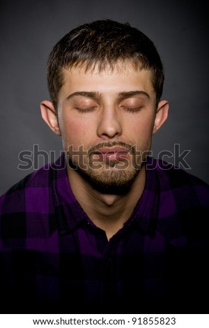 portrait of a nice guy with a stylish beard, with eyes closed - stock photo