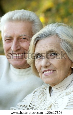 portrait of a nice seniors standing in autumn park