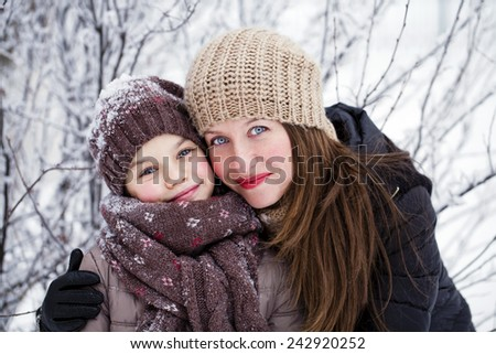 Portrait of a nine year girl with her mother in winter park - stock photo